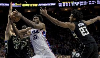 Philadelphia 76ers' Joel Embiid, center, drives to the basket as he splits between Milwaukee Bucks' Matthew Dellavedova, left, of Australia, and Sterling Brown during the second half of an NBA basketball game Saturday, Jan. 20, 2018, in Philadelphia. The 76ers won 116-94. (AP Photo/Chris Szagola)