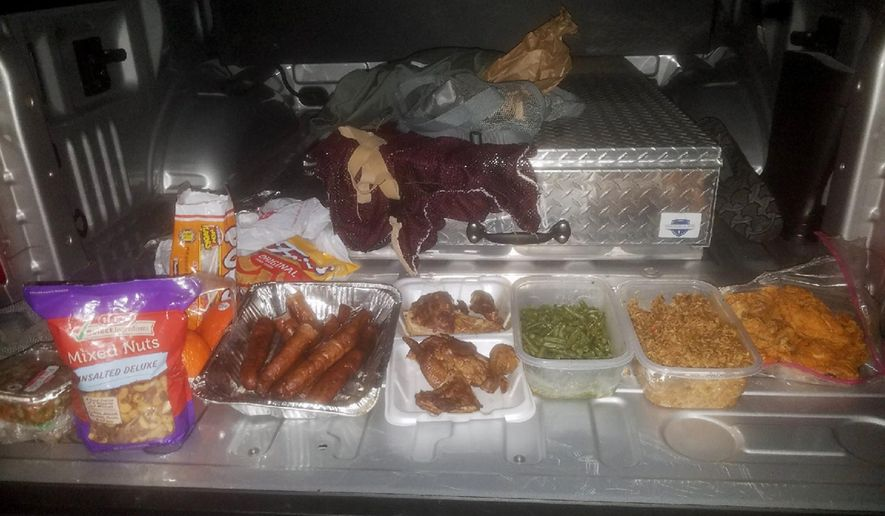This Wednesday, Jan, 24, 2018, photo provided by the Jefferson County Sheriff's Office in Beaumont, Texas, shows home-cooked treats taken from federal inmate Joshua Hansen, after he escaped from a federal prison near Beaumont with the intention of breaking back in laden with a duffle bag with bottles of alcohol and home-cooked treats. He was arrested Jan. 24, as he ran onto private land near the prison. (Jefferson County Sheriff's Office via AP)