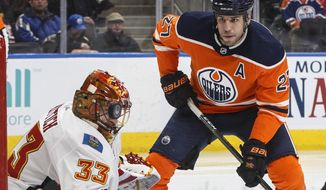 Calgary Flames goaltender David Rittich (33) makes a stop with his mask as Edmonton Oilers left wing Milan Lucic (27) looks for the rebound during second-period NHL hockey game action in Edmonton, Alberta, Thursday, Jan. 25, 2018. (Jason Franson/The Canadian Press via AP)