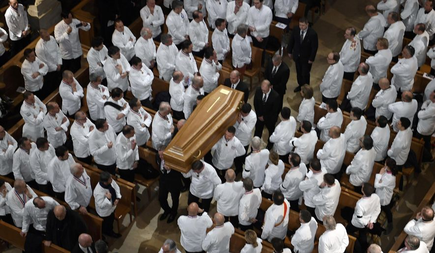 Chefs carry the coffin of French Paul Bocuse during a funeral ceremony at the Saint-Jean Cathedral in Lyon, central France, Friday, Jan. 26, 2018. Hundreds of chefs and French dignitaries are gathering in the culinary mecca of Lyon for the funeral of Paul Bocuse, a master chef who defined French cuisine for more than a half-century and put it on tables around the world. (Philippe Desmazes/Pool Photo via AP)
