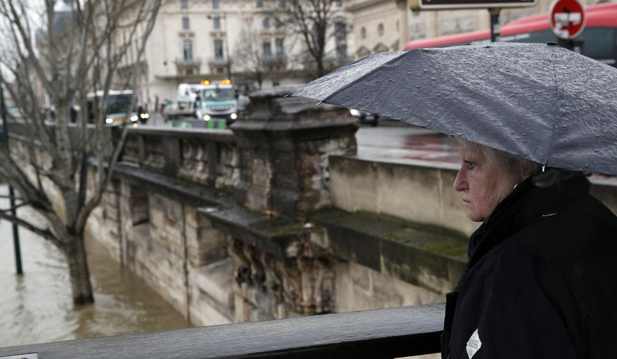 A woman watches the flooded banks of river Seine in Paris, Thursday, Jan.25, 2018. Rivers across France kept swelling as more rain hit the country Thursday, with 15 departments across the country remaining on alert for floods. In addition to Paris, where the Seine river is expected to keep rising until Saturday, the other regions threatened are in the north and east of the country. (AP Photo/Christophe Ena)