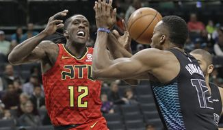 Atlanta Hawks' Taurean Prince, left, is fouled as he drives against Charlotte Hornets' Dwight Howard during the first half of an NBA basketball game in Charlotte, N.C., Friday, Jan. 26, 2018. (AP Photo/Chuck Burton)
