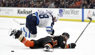 Winnipeg Jets' Bryan Little, top, and Anaheim Ducks' Hampus Lindholm, of Sweden, fall to the ice while fighting for the puck during the first period of an NHL hockey game Thursday, Jan. 25, 2018, in Anaheim, Calif. (AP Photo/Jae C. Hong)