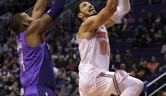New York Knicks center Enes Kanter (00) drives past Phoenix Suns center Greg Monroe during the first half of an NBA basketball game Friday, Jan. 26, 2018, in Phoenix. (AP Photo/Rick Scuteri)