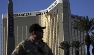 In this Oct. 3, 2017, file photo, a Las Vegas police officer stands by a blocked off area near the Mandalay Bay casino in Las Vegas. (AP Photo/John Locher, File)