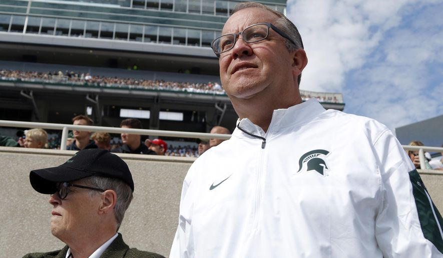 FILE - In this Sept. 24, 2016, file photo, Michigan State University athletics director Mark Hollis, right, and president Lou Anna Simon watch the action during an NCAA college football game against Wisconsin, in East Lansing, Mich. Hollis has built a reputation on the foundation of innovation at Michigan State, putting hockey and basketball games in football stadiums. His legacy, though, may be marred by Larry Nassar. A day after Michigan State President Lou Anna Simon resigned amid an outcry over the school's handling of allegations against the disgraced doctor, Hollis' future as its athletic director may be tenuous. (AP Photo/Al Goldis, File)