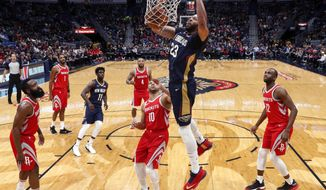 New Orleans Pelicans forward Anthony Davis (23) dunks over Houston Rockets guard Eric Gordon (10) during the first half of an NBA basketball game in New Orleans, Friday, Jan. 26, 2018. (AP Photo/Gerald Herbert)
