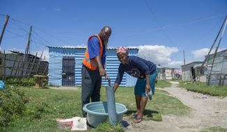 """People collect water from a communal tap at an informal settlement near Cape Town, South Africa, Tuesday, Jan. 23, 2018, as a harsh drought may force South Africa's showcase city of Cape Town to turn off most of its taps.  While the city urges people to restrict water usage, many living in poor areas already have limited access to water, and the day that the city runs out of water, ominously known as """"Day Zero"""", moves ever closer for the nearly 4 million residents.  (AP Photo)"""