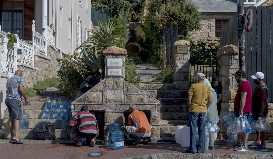 """People queue to collect water from a natural spring in the Cape Town, South Africa, suburb of St. James, Saturday Jan. 20, 2018.  Tourists in the city famously perched near two oceans are being asked to flush the toilet as little as possible and swim in the ocean instead of pools """"and maybe even spare yourself a shower"""", as a harsh drought may force South Africa's showcase city to turn off most taps. (AP Photo)"""