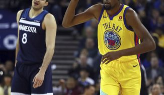 Golden State Warriors' Kevin Durant, right, celebrates a score as Minnesota Timberwolves' Nemanja Bjelica reacts during the first half of an NBA basketball game Thursday, Jan. 25, 2018, in Oakland, Calif. (AP Photo/Ben Margot)