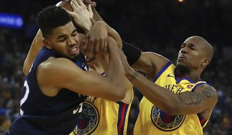 Minnesota Timberwolves' Karl-Anthony Towns, left, fights for the ball with Golden State Warriors' David West, right, and Klay Thompson during the first half of an NBA basketball game Thursday, Jan. 25, 2018, in Oakland, Calif. (AP Photo/Ben Margot)