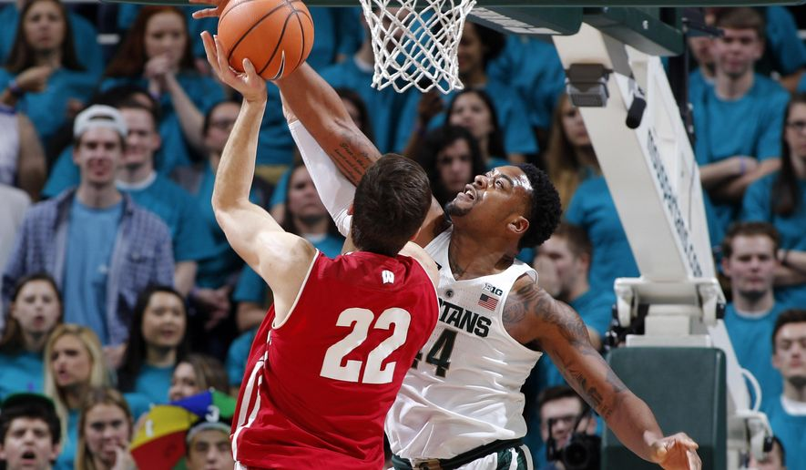Michigan State's Nick Ward, right, blocks a shot by Wisconsin's Ethan Happ (22) during the first half of an NCAA college basketball game Friday, Jan. 26, 2018, in East Lansing, Mich. (AP Photo/Al Goldis)