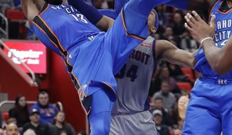 Oklahoma City Thunder forward Paul George (13) falls after Detroit Pistons forward Tobias Harris (34) deflected the ball out of his control during the second half of an NBA basketball game Saturday, Jan. 27, 2018, in Detroit. (AP Photo/Carlos Osorio)