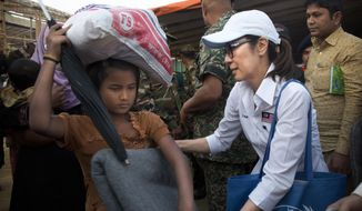 Malaysian actress Michelle Yeoh, right, distributes blanket to a Rohingya refugee at Balukhali refugee camp near Cox's Bazar, Bangladesh, Saturday, Jan. 27, 2018. A special delegation led by Michelle Yeoh and Malaysian Armed Forces Chief Gen. Raja Mohamad Affandi Saturday visited Rohingya refugee camp and distributed relief material items apart from evaluating the impact of the aid. (AP Photo/Manish Swarup)