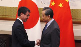 Japanese Foreign Minister Taro Kono, left, shakes hands with Chinese counterpart Wang Yi before their meeting at the Diaoyutai State Guesthouse in Beijing, Sunday, Jan. 28, 2018. (AP Photo/Andy Wong, Pool)