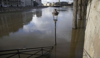 The banks of river Seine are flooded in Paris, France, Friday, Jan. 26, 2018. The Paris region has been deeply affected by the floods that hit the country over the past week, but in Paris, it was business as usual. (AP Photo/Michel Euler)