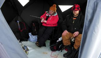 """In this Wednesday, Jan. 17, 2018 photo, Elizabeth Reed and Alex Krier ice fish on Holter Lake, in Mont. """"I love it,"""" Krier said.  (Rion Sanders/The Great Falls Tribune via AP)"""