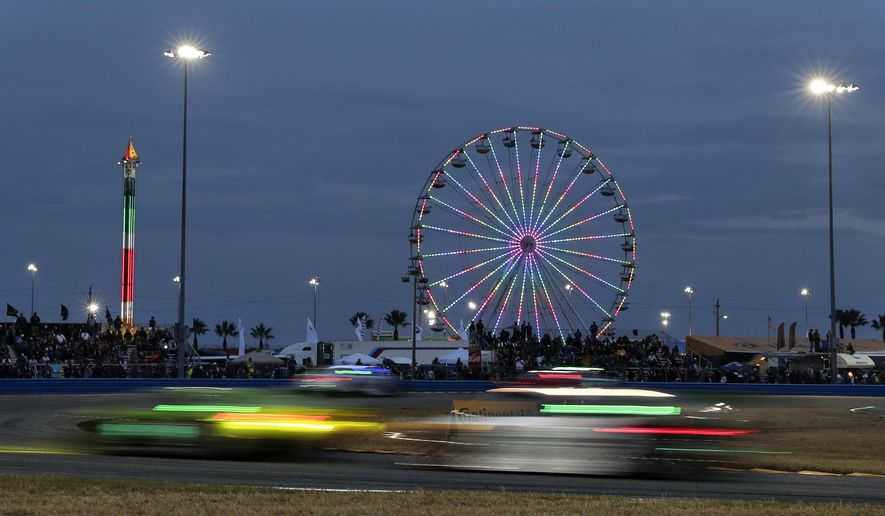 Cars head through a turn in the early evening hours during the IMSA 24-hour auto race at Daytona International Speedway, Saturday, Jan. 27, 2018, in Daytona Beach, Fla. (AP Photo/John Raoux)