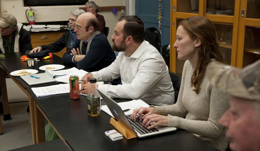 """In this photo taken Jan. 10, 2018, from right at center, researchers Katie Whipkey, Ryan Brown and Rob Lempert gather comments at the Sitka Sound Science Center in Sitka, Alaska. While researching landslide preparedness in Sitka, RAND Corporation investigators have found a shared concern among Sitkans about the future of housing availability in the community. Researchers Brown, Lempert and Whipkey made their second trip to Sitka under a yearlong planning grant from the National Science Foundation's """"Smart and Connected Communities Program."""" (James Poulson/Daily Sitka Sentinel via AP)"""