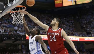 North Carolina's Theo Pinson (1) drives to the basket while North Carolina State's Omer Yurtseven (14) defends during the first half of an NCAA college basketball game in Chapel Hill, N.C., Saturday, Jan. 27, 2018. (AP Photo/Gerry Broome)