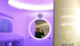 In this Jan. 11, 2018 photo, Chief Revenue Officer Kyle Diercks is reflected in the mirror of the Solius machine, which shines an isolated spectrum of light designed to promote production of vitamin D, at the company headquarters on Bainbridge Island, Wash. (AP Photo/Meegan M. Reid/Kitsap Sun)