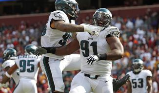 FILE - In this Sept. 10, 2017, file photo, Philadelphia Eagles defensive tackle Fletcher Cox, right, celebrates with Derek Barnett after officials reviewed and confirmed a play in which Washington Redskins quarterback Kirk Cousins fumbled the ball and Cox recovered and returned it for a touchdown in the second half of an NFL football game in Landover, Md. The Eagles and the New England Patriots are set to meet in Super Bowl 52 on Sunday, Feb. 4, 2018, in Minneapolis. (AP(AP Photo/Alex Brandon, File)