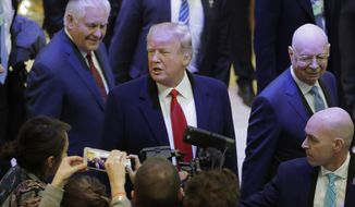 U.S. President Donald Trump talks to journalists as U.S. Secretary of State Rex Tillerson, left, and WEF founder Klaus Schwab walk past during the annual meeting of the World Economic Forum in Davos, Switzerland, Friday, Jan. 26, 2018. (AP Photo/Markus Schreiber)