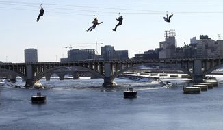 Zipline enthusiasts, including politicians, celebrities and media, cross the Mississippi River in Minneapolis Friday, Jan. 26, 2018 as the 10-day Bold North theme festival got underway, one of many events leading up to the Super Bowl. (AP Photo/Jim Mone)