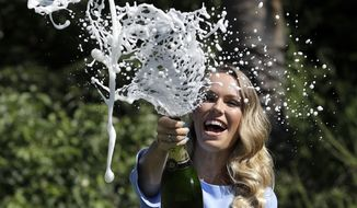Denmark's Caroline Wozniacki sprays champagne during a photo shoot in the Royal Botanical Gardens in Melbourne, Australia, Sunday, Jan. 28, 2018. Wozniacki defeated Romania's Simona Halep in Saturday's final to win the Australian Open women's singles final.(AP Photo/Dita Alangkara)
