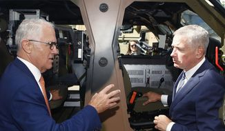 Australia Prime Minister Malcolm Turnbull, left, talks to Thales CEO Chris Jenkins during a visit to Thales Underwater Systems in Sydney, Monday, Jan. 29, 2018. The government announced a new strategy to boost Australia into the ranks of the top 10 defense industry exporting countries within a decade through arms sales to liked-minded nations and with safeguards to keep weapons out of the hands of rogue regimes. (Daniel Munoz/AAP Image via AP)