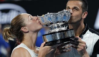 Canada's Gabriela Dabrowski, left, and Croatia's Mate Pavic kiss their trophy after defeating Hungary's Timea Babos and India's Rohan Bopanna in the mixed doubles final at the Australian Open tennis championships in Melbourne, Australia, Sunday, Jan. 28, 2018. (AP Photo/Vincent Thian)