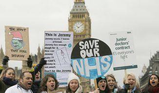 FILE - In this Wednesday, Feb. 10, 2016 file photo, Junior National Health Service (NHS) doctors wave placards referring to British Conservative Party Secretary of State for Health, Jeremy Hunt, during a protest outside St Thomas Hospital in London. This winter has brought a daily drip of grim stories from Britain's health care system, and experts say alarm bells should be ringing across the entire system. (AP Photo/Frank Augstein, file)