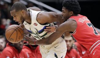 Milwaukee Bucks forward Khris Middleton, left, drives against Chicago Bulls guard Justin Holiday during the first half of an NBA basketball game Sunday, Jan. 28, 2018, in Chicago. (AP Photo/Nam Y. Huh)