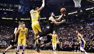 Toronto Raptors guard Fred VanVleet (23) shoots while falling as Los Angeles Lakers guard Jordan Clarkson (6) defends during first-half NBA basketball game action in Toronto, Sunday, Jan. 28, 2018. (Frank Gunn/The Canadian Press via AP)