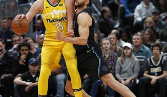 Denver Nuggets center Nikola Jokic, left, looks to pass the ball as Dallas Mavericks forward Maximilian Kleber defends during the first half of an NBA basketball game Saturday, Jan. 27, 2018, in Denver. (AP Photo/David Zalubowski)