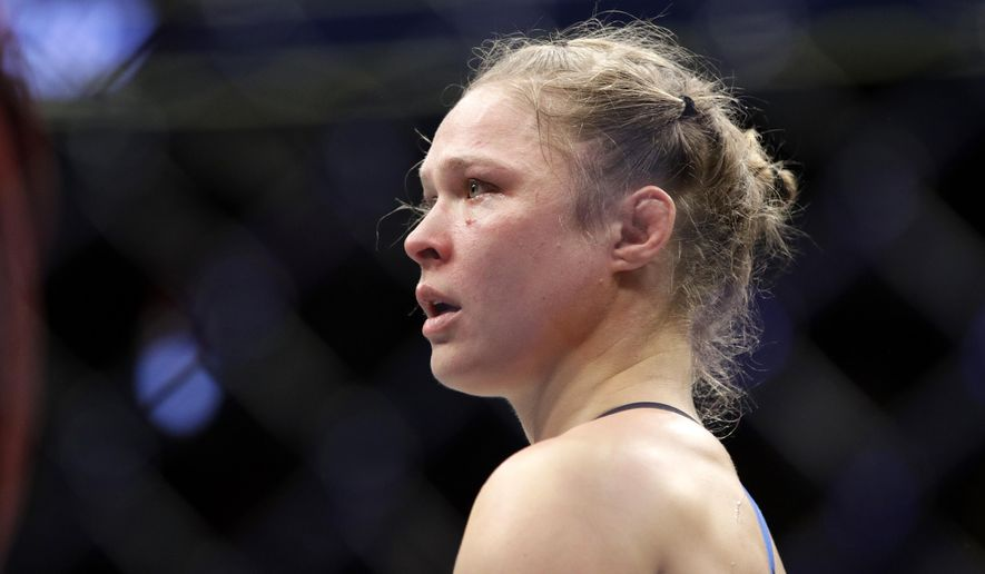 In this Dec. 30, 2016, file photo, Ronda Rousey stands in the cage after Amanda Nunes forced a stoppage in the first round of their women's bantamweight championship mixed martial arts bout at UFC 207 in Las Vegas. (AP Photo/John Locher) ** FILE **
