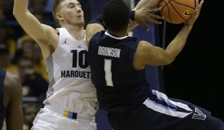 Marquette's Sam Hauser (10) is called for a foul as Villanova's Jalen Brunson tries to shoot during the first half of an NCAA college basketball game Sunday, Jan. 28, 2018, in Milwaukee. (AP Photo/Tom Lynn)