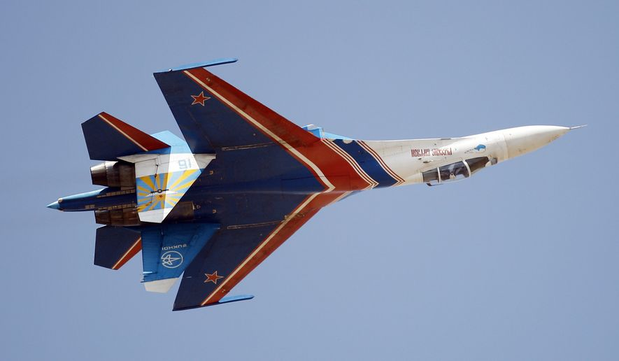 Russian air force air demonstration team, Russian Knights' Sukhoi Su-27  displays an inverted flight during the last day of the Aero India 2013 at Yelahanka air base in Bangalore, India, Sunday, Feb. 10, 2013. More than 600 aviation companies along with delegations from 78 countries took part in the five-day event. (AP Photo/Aijaz Rahi)