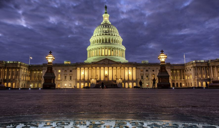 In this Jan. 21, 2018, file photo, lights shine inside the U.S. Capitol Building as night falls in Washington. (AP Photo/J. David Ake) ** FILE **