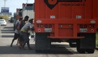 In this Jan. 23, 2018 photo, men try to steal rice from a cargo truck arriving to the port in Puerto Cabello, Venezuela. Sporadic looting, food riots and protests driven by hunger have surged in Venezuela, a country that's no stranger to unrest. (AP Photo/Fernando Llano)