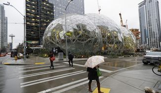 Pedestrians walk past the Amazon Spheres in downtown Seattle on the day of the grand opening of the geodesic domes, which will primarily serve as a working and gathering space for Amazon.com employees, Monday, Jan. 29, 2018, in Seattle. (AP Photo/Ted S. Warren)