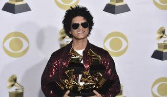 "Bruno Mars poses in the press room with his awards for best R&B album, record of the year, album of the year, best engineered album, non-classical, for ""24K Magic,"" and song of the year, best R&B performance and best R&B song, for ""That's What I Like"" at the 60th annual Grammy Awards at Madison Square Garden on Sunday, Jan. 28, 2018, in New York. (Photo by Charles Sykes/Invision/AP)"