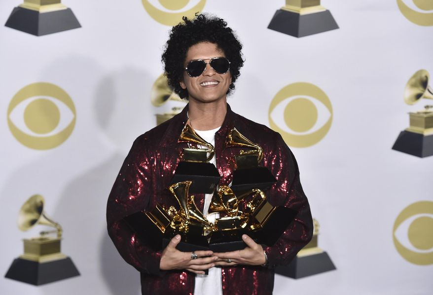"""Bruno Mars poses in the press room with his awards for best R&B album, record of the year, album of the year, best engineered album, non-classical, for """"24K Magic,"""" and song of the year, best R&B performance and best R&B song, for """"That's What I Like"""" at the 60th annual Grammy Awards at Madison Square Garden on Sunday, Jan. 28, 2018, in New York. (Photo by Charles Sykes/Invision/AP)"""