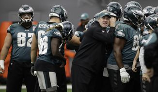 FILE - In this Jan. 26, 2018, Philadelphia Eagles head coach Doug Pederson huddles with the team during practice at the team's NFL football training facility in Philadelphia.  Pederson is one win away from bringing Philadelphia the elusive Super Bowl title his mentor couldn't deliver. If the Eagles beat New England on Sunday, Feb. 4 Pederson will hoist the Vince Lombardi Trophy and Philadelphia would celebrate its first NFL title since beating Lombardi's Green Bay Packers in 1960. (AP Photo/Matt Rourke, File)