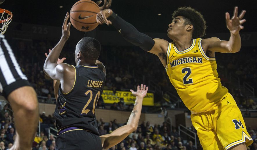 Northwestern guard Scottie Lindsey (20) has his shot-attempt blocked by Michigan guard Jordan Poole (2) in the first half of an NCAA college basketball game at Crisler Center in Ann Arbor, Mich., Monday, Jan. 29, 2018. (AP Photo/Tony Ding)