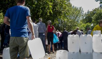 In this photo taken Tuesday, Jan. 23, 2018, people queue for water at a natural spring in Cape Town, South Africa.  A charity announced Monday Jan. 29, 2018, it is organizing a nationwide collection of bottled water for stockpiling in military bases in and around the tourist city which might have to turn off most taps in April because of a prolonged drought. (AP Photo)