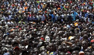 "Supporters of opposition leader Raila Odinga, one wearing a mask, attend a mock ""swearing-in"" ceremony at Uhuru Park in downtown Nairobi, Kenya Tuesday, Jan. 30, 2018. Odinga was sworn-in as ""the people's president"" during a mock ""inauguration"", in protest of President Uhuru Kenyatta's new term following the divisive 2017 election, and despite the government's warning that the event would be considered treason. (AP Photo/Ben Curtis)"