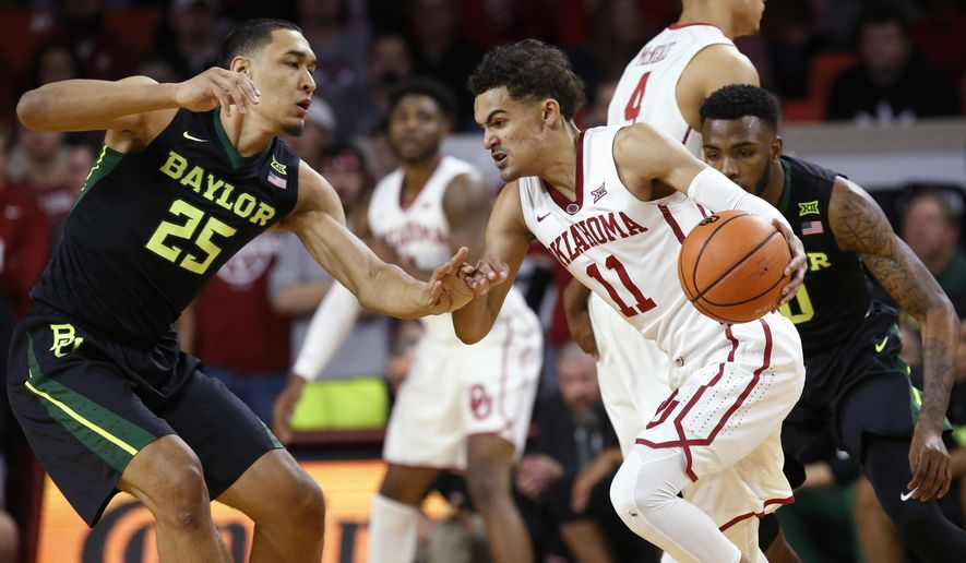 Oklahoma guard Trae Young (11) drives between Baylor forward Tristan Clark (25) and guard Tyson Jolly, right, during the first half of an NCAA college basketball game in Norman, Okla., Tuesday, Jan. 30, 2018. (AP Photo/Sue Ogrocki)