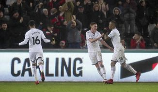 Swansea City's Jordan Ayew, right, celebrates scoring his side's second goal of the game during the English Premier League soccer match between Swansea City and Arsenal at the Liberty Stadium, Swansea, Wales, Tuesday, Jan. 30, 2018. (Nick Potts/PA via AP)