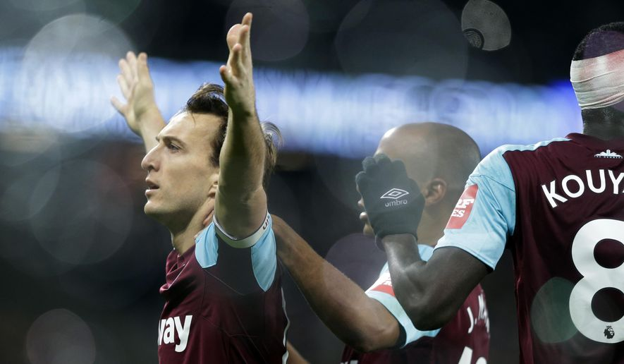 West Ham United's Mark Noble, left, celebrates after scoring from the penalty sport for his side's first goal during their English Premier League soccer match between West Ham United and Crystal Palace at the London stadium in London, Tuesday, Jan. 30, 2018. (AP Photo/Alastair Grant)